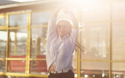 Girl in a shirt and sunglasses. Young attractive girl in a white shirt and sunglasses. She stands on the city street and smiles. The girl raised her hands up Royalty Free Stock Photography