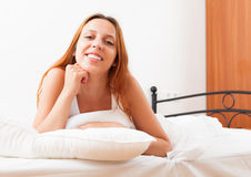 Girl in shirt   wakes up on the white sheets Stock Images