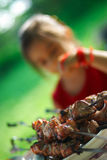 Girl and  shish kebab. The little girl sits and thinks: it is necessary to eat a shish kebab or it is not necessary Royalty Free Stock Photography