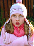 Girl shivering. A young girl wearing a winter hat, shivering in cold weather Stock Photo