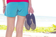 Girl with shoes on beach Royalty Free Stock Photo