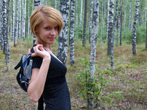 Girl with shoes in hand. And birch grove in background Stock Photography
