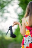 Girl with shoes in hand Stock Image