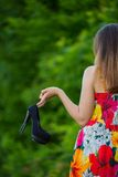 Girl with shoes in hand Stock Photography