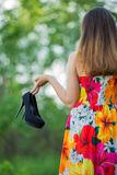Girl with shoes in hand Royalty Free Stock Photos