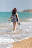 Girl with shoes in hands walks on surf line Royalty Free Stock Images