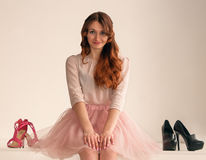 Girl and shoes. Red-haired girl and two pairs of shoes Royalty Free Stock Photography