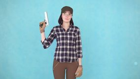 Girl shooter with gun and glasses looking at camera smiling. Portrait of a woman shooter with a gun and glasses looking at the camera smiling isolate on blue stock video