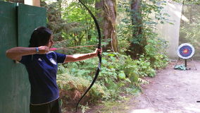 Girl Shooting Bow and Arrow. Young girl shooting bow and arrow into target. Archery range in the forest Royalty Free Stock Photos