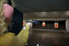 Girl shooting gun. Girl target shooting at gun range stock images
