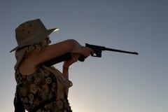 Girl shooting gun outdoors Stock Photography