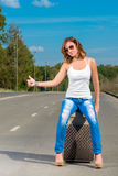 Girl shooting with a suitcase on the road Stock Image