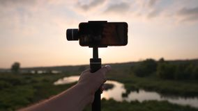 The girl shooting video at sunset with smartphone on the stabilizer, slow motion. The girl shooting video of the beautiful nature, pond and meadow at sunset with stock video footage