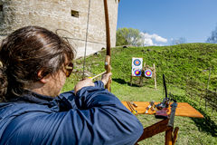 Girl shoots arrows from the walls of the fortress in Staraya Lad Stock Photo
