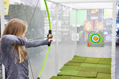 Girl shoots bow in children`s shooting range Royalty Free Stock Photos