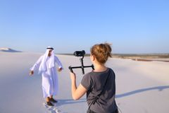 Girl shoots on camera dancing Muslim man in spacious desert on h royalty free stock photo