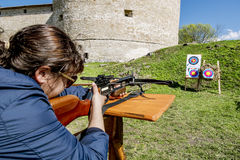 Girl shoots a crossbow from the walls of the fortress in Staraya Royalty Free Stock Image
