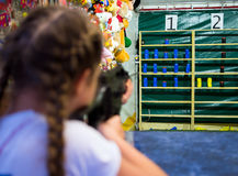 The girl shoots from an pneumatic machine in the prize dash.  stock photo