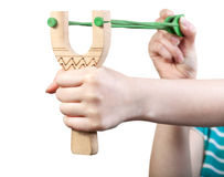 Girl shoots from simple wooden slingshot Royalty Free Stock Photo