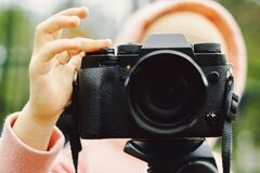 Girl shoots on a vintage film camera close-up on the background of forest
