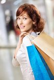 Girl in shop. Portrait of happy girl standing in a half-turn with packages in shop Royalty Free Stock Photography