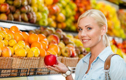 Girl at the shop choosing fruits hands apple Royalty Free Stock Image