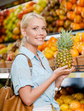 Girl at the shop choosing fruits hands pineapple Royalty Free Stock Photos