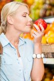 Girl at the shop choosing fruits smells apple Stock Photography