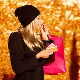 Girl with shopping bag. Photo of cute blond girl with pink shopping bag, side view of pretty woman holding paper present bag, beautiful happy shopper over autumn Royalty Free Stock Image