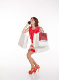 Girl with shopping bags calling by mobile phone Royalty Free Stock Photo