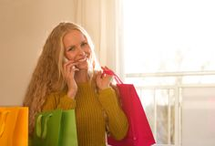 Girl with shopping bags and cell phone. Pretty young woman talking on phone and holding shopping bag on shoulder Stock Photo