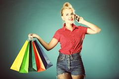 Girl with shopping bags and cell phone retro style Royalty Free Stock Photo
