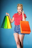 Girl with shopping bags and cell phone retro style Stock Photography