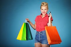 Girl with shopping bags and cell phone retro style Royalty Free Stock Images