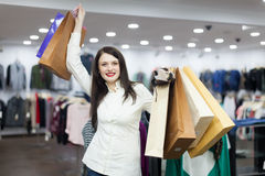 Girl with shopping bags at clothing store. Happy brunette girl with shopping bags at clothing store Royalty Free Stock Photography
