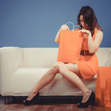 Girl with shopping bags on couch Royalty Free Stock Images