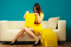 Girl with shopping bags on couch Stock Photography
