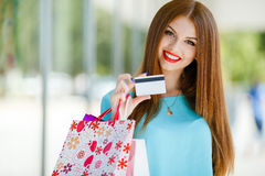 Girl with shopping bags and credit card. Stylish,fashionable, beautiful woman with long straight red hair, and brown eyes,wearing a blue blouse, spends time in Royalty Free Stock Photography