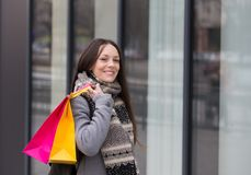 Girl with shopping bags. Happy shopaholic girl with shopping bags standing in front of fashion mall stock images