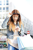 Girl with shopping bags looking message on phone, outdoor. Royalty Free Stock Photography