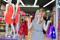 Girl with shopping bags out of the store Stock Photos