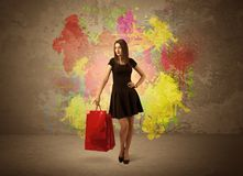 Girl with shopping bags and paint splatter. A happy young elegant woman standing with shopping bags in front of brown wall background full of colorful ink Stock Photos