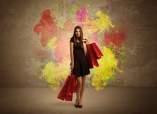 Girl with shopping bags and paint splatter. A happy young elegant woman standing with shopping bags in front of brown wall background full of colorful ink Stock Image