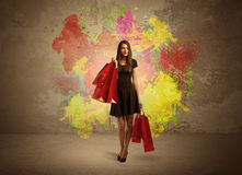 Girl with shopping bags and paint splatter. A happy young elegant woman standing with shopping bags in front of brown wall background full of colorful ink Royalty Free Stock Image