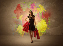 Girl with shopping bags and paint splatter. A happy young elegant woman standing with shopping bags in front of brown wall background full of colorful ink Royalty Free Stock Photo