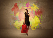 Girl with shopping bags and paint splatter. A happy young elegant woman standing with shopping bags in front of brown wall background full of colorful ink Stock Images