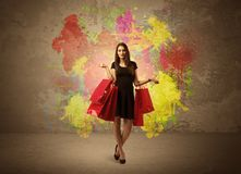 Girl with shopping bags and paint splatter. A happy young elegant woman standing with shopping bags in front of brown wall background full of colorful ink Royalty Free Stock Images
