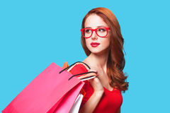 Girl with shopping bags. Redhead girl with shopping bags on blue background royalty free stock photography