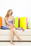 Girl with shopping bags on sofa Stock Photo