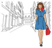 Girl with shopping bags walking on a small street Stock Photography
